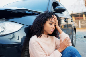 Black woman leaning against a car holding her head after a crash