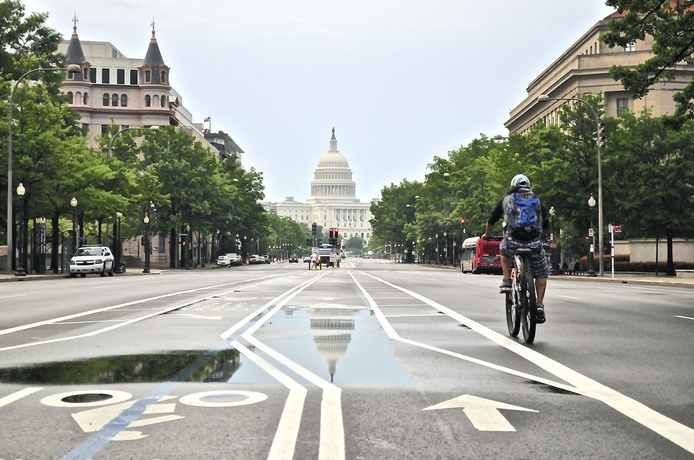 cyclist on street heading to capitol building