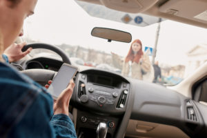 Distracted young male driver looking at the screen of his mobile phone while almost running over a pedestrian.