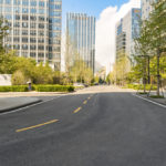 An empty roadway leading to a downtown urban area