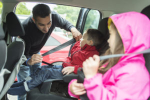 Father putting seat belts on his children