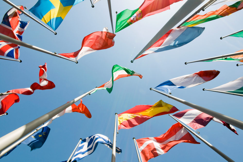 Various international flags waving from flagpoles