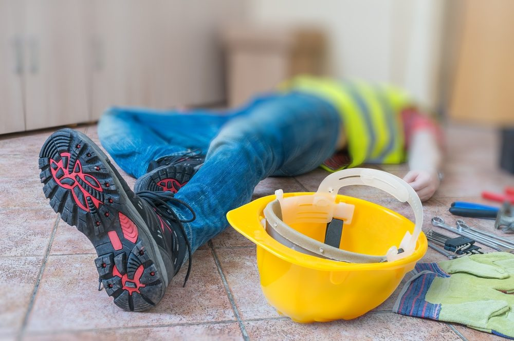 Construction worker laying on ground after injury with hard hat and gloves nearby