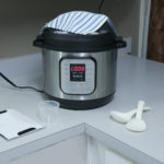 Instant pot on a countertop with a towel resting on top