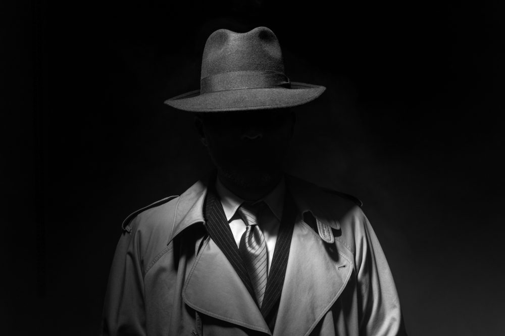 A well dressed man in a fedora, his face completely hidden in shadow