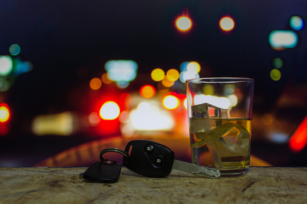 keys and an alcoholic beverage with car lights in background