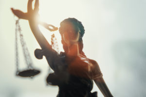 Statue of lady justice with sunlight shining behind