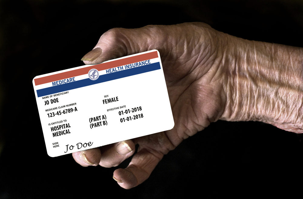 An elderly female hand holds a mock United State government Medicare Health Insurance card.