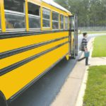 Students hop off a yellow school bus at a school bus stop