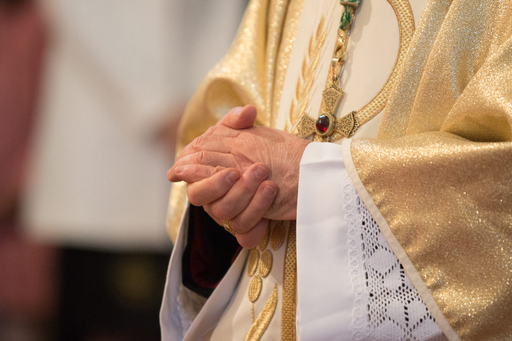 Catholic priest with his hands clasped together