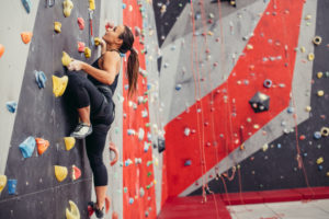 An athletic woman scaling a rock wall at an indoor gym