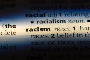 "The word ""racism"" highlighted in a dictionary"