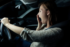 A woman yawns as she drives her car at night