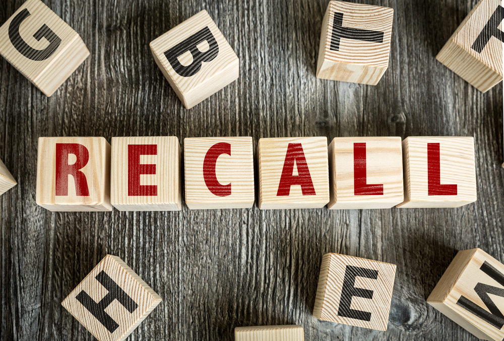 Wooden block spelling the word RECALL