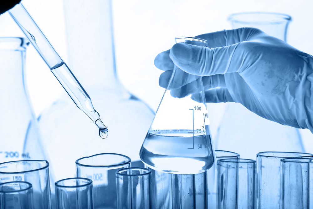 A gloved hand holds a flask of clear liquid with other vessels in the background