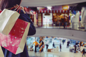 Woman holding shopping bags at a crowded mall