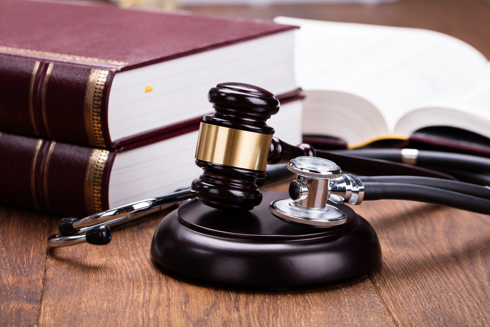 A stethoscope lays next to a gavel and books