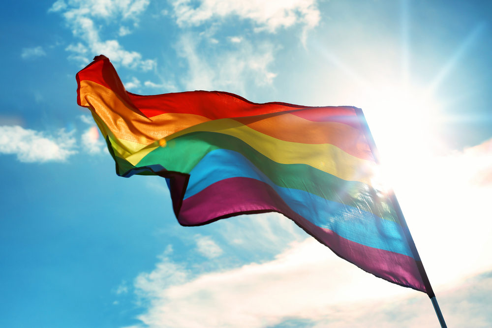 A rainbow flag flapping against a bright sun and blue sky