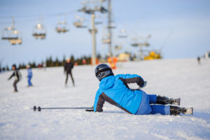 Young woman skier in blue ski suit after the fall on mountain slope trying get up against ski-lift.