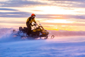 A man is riding snowmobile in mountains
