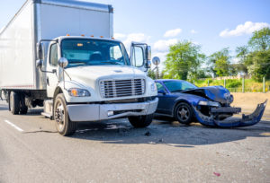Collision of a semi truck with box trailer and a passenger car on the highway road