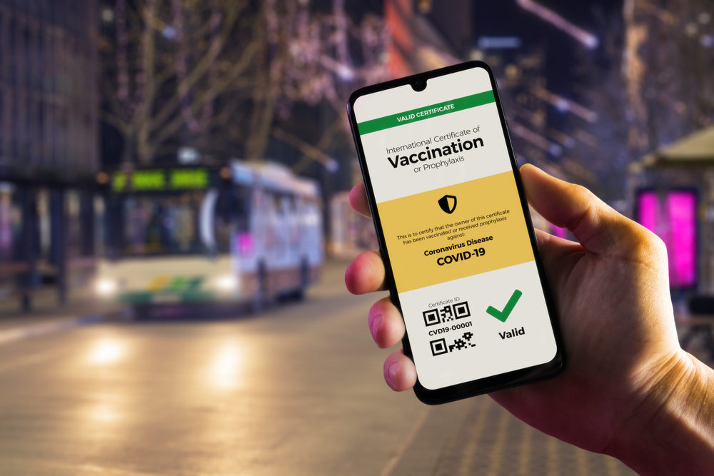 Smartphone displaying a valid digital vaccination certificate for COVID-19 in male's hand, downtown and city bus in background.