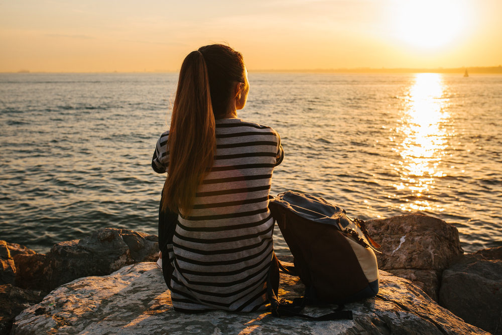 A young tourist girl with a backpack sits on the rocks next to the sea at sunset and looks into the distance.