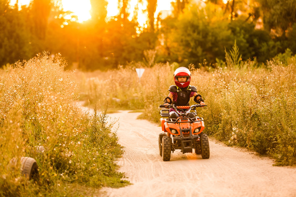 The little girl rides a quad bike ATV