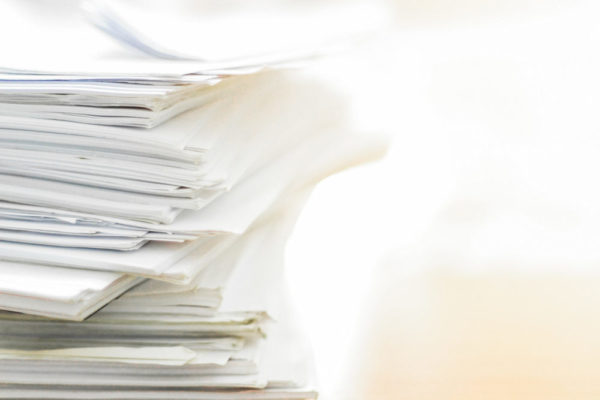 Large stack of legal documents piled on a desk