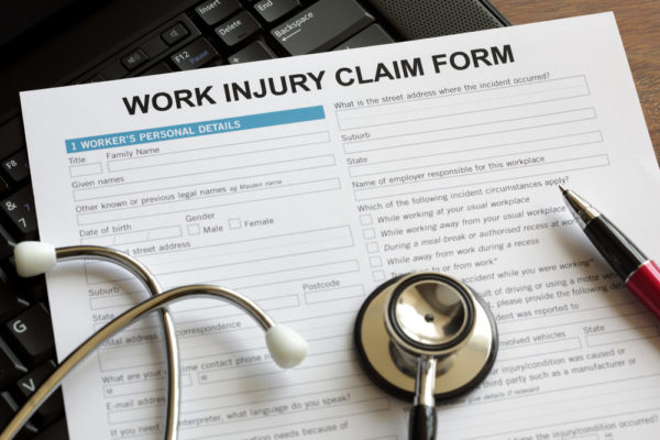 A stethoscope and pen rest atop a Work Injury Claim Form document