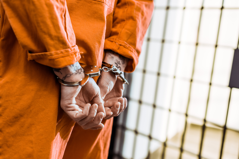 A prisoner in an orange prison jumpsuit and handcuffs