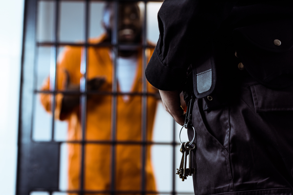 security guard standing near prison bars with keys