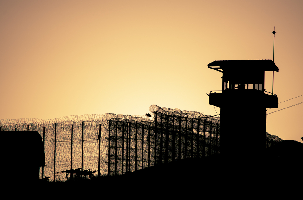 Silhouette of barbed wires and watchtower of prison, at sunset