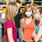 Students near a school bus wearing medical masks.