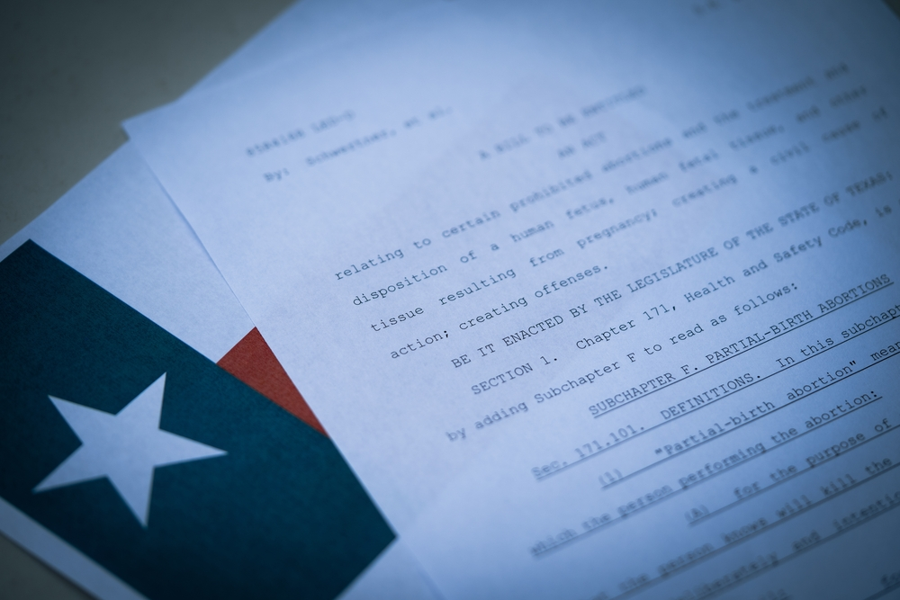 Blurred Close up view of Texas Abortion Law next to the flag of Texas